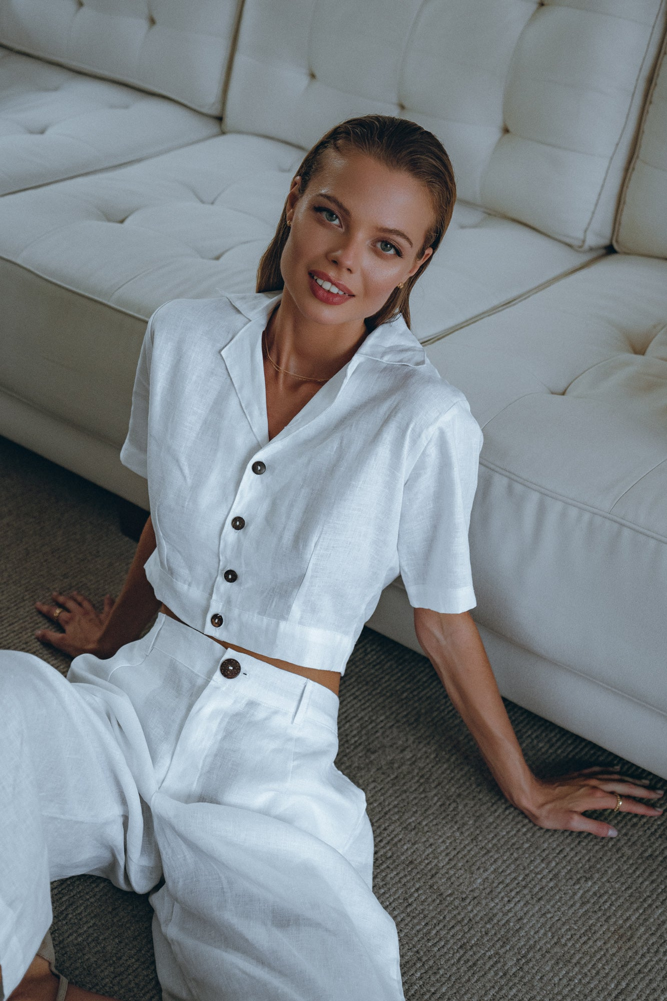 model who is smiling into the camera is dressed in a white linen shirt and white matching pants