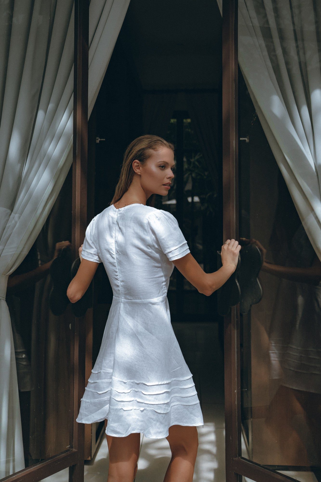 girl going to her beach house wearing white linen mini dress