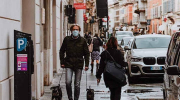 Man with mask walking his dog during coronavirus pandemic