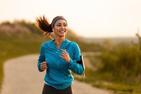 Dedicated athletic woman running in nature and dawn.