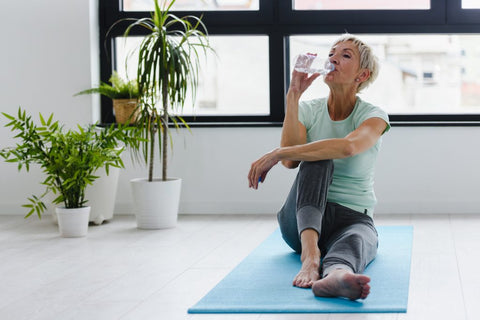 Beautiful senior woman drinking water after exercise