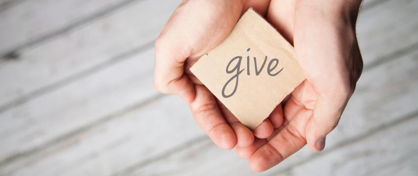 Cupped hands, holding wood square, with the word give written on it,