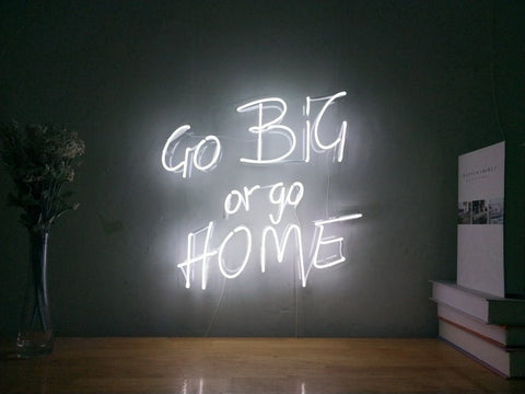 LED sign on an internal wall which reads 'GO BIG or GO HOME'