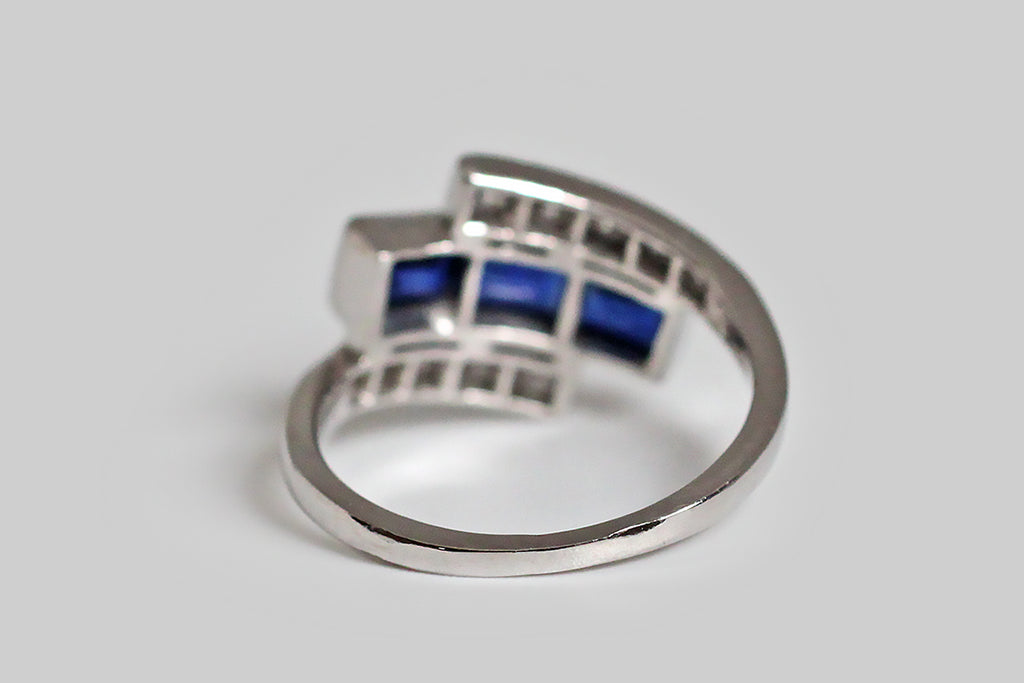 An Art Deco era ring, modeled in 18k white gold, whose diamond-set bypass shank cradles a long, rectangular arrangement of three bezel-set sapphires. These vibrant, created blue gems are set end to end inside their long bezel, and the early modern brilliant cut diamonds that frame them are bead set. This elegant ring is all original and its condition is outstanding— it would make a lovely anniversary ring (three year or five year), or alternative wedding band.