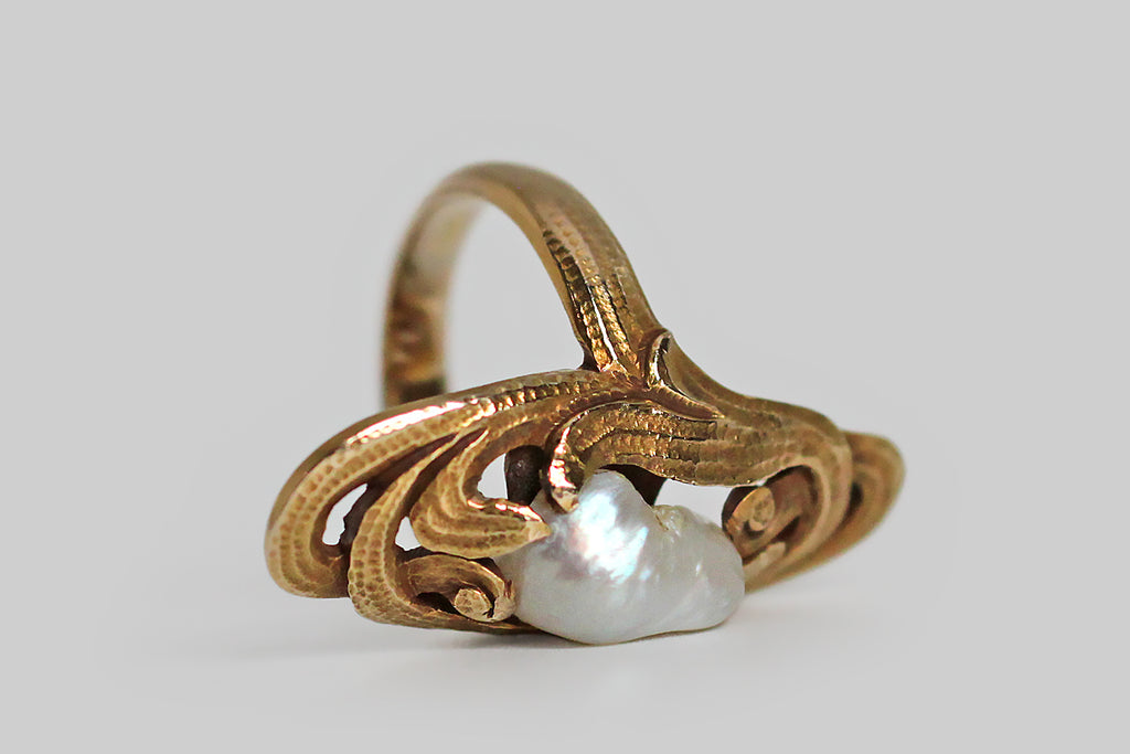 "An Arts & Crafts period shield-shaped ring, modeled in 14k yellow gold, whose natural, baroque, saltwater pearl hovers amid a colony of swirling fronds. These naturalistic forms are hand-built, and their hand-applied hammered texture is especially striking. They also function as ""prongs,"" holding the pearl in place. Larger, natural, old, saltwater pearls like this one are becoming a rarity— this one is white; it has a lovely iridescent (rainbow) lustre, compelling shape and texture."