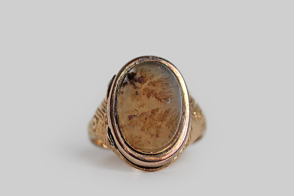 A soulful, Victorian-era locket ring, made in 14k yellow gold, whose hinged face is set with a fine, buff-polished slab of dendritic agate. This bezel-set agate is slightly translucent, with earthy, fern-like, dendrite forms that float in its light field. The ring's shoulders feature a deeply engraved diamond pattern; its weighty, half-round shank tapers from the shoulder toward the base. Rings from this era with locket faces are quite rare.