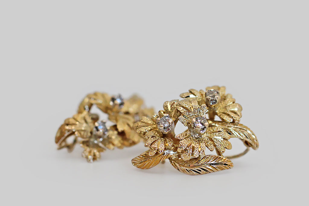 A pair of retro-era drop earrings, modeled in 14k yellow gold, each one a stem of three cascading flowers and their leaves. These little flowers are beautifully constructed, with outstanding three-dimensional depth, and dramatic contrasting textures. Each flower's center is set with a single-cut white diamond; these diamonds are held in four prong white gold settings.
