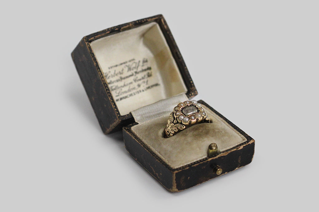 An antique ring, made in 15k gold, to memorialize the life of M. Snowdon. This ring features ornate, creaturely, floral decor that is typical of the Georgian period. Resting between these two branching moth-like forms, is a rectangular crystal face, with a natural seed pearl surround. Carefully plaited locks of human hair lie beneath the crystal. The seed pearls range in color along an interesting golden/earthy palate that we especially like with the yellow gold.