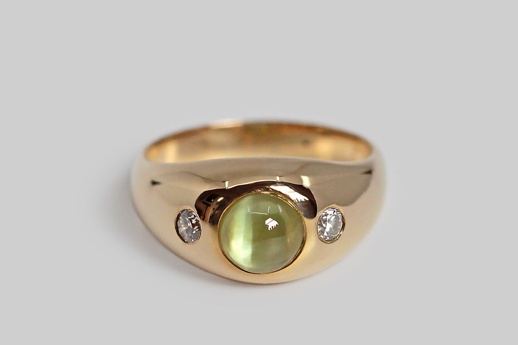 An especially winning vintage gypsy ring, with a rounded, tapering profile, made in 14k yellow gold and set with a striking cats eye chrysoberyl gem. This chrysoberyl is vibrantly golden-green, with a straight well-defined eye that shifts with movement. The cats eye is flanked by a pair of brilliant cut white diamonds