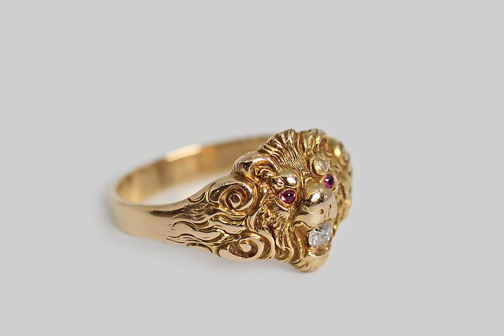 A rare and especially handsome Victorian-era lion mask ring, finely made in 18k yellow gold. The modeling of this fierce little face is expressive, deeply carved, and full of movement— the lion's eyebrows knit above his cabochon ruby eyes, giving him a challenging expression, and his curling mane trails off into the ring's shoulders. Our golden friend holds a white diamond in his mouth. This ring has a weighty, flat, medium-width shank. It is well-suited to all genders.