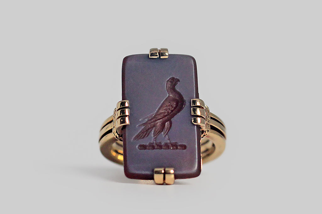 A turn-of-the-century (20th) intaglio ring of rare quality, made in 18k yellow gold and featuring the most beautiful, finely-detailed, hardstone carving of a falcon. This romantic figure is hand carved into a rectangular sard slab (sard is an earthy-red variety of chalcedony). He is very dignified, with his breast thrust forward. The hook in his beak is crisp and clear, as are the tiny feathers of his wings. This rectangular gem is held securely in squared groups of prongs
