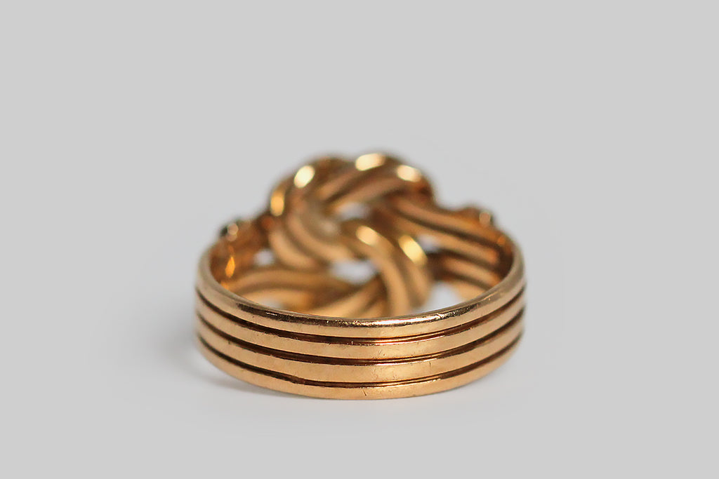 "A striking Victorian-era wide band ring, modeled in 18k rosy yellow gold, whose face is a pair of sailor's reef knots, laid one atop the other. These lovely, sinuous knots are each ""tied"" using pairs of gold wires, and these wires come together in a stack of four to form the ring shank. They are decoratively bound, with vertical straps, at the ring's shoulders. Knot motifs from this era symbolized loyalty, fidelity, and the strength of a bond. This ring is fully hallmarked for Sheffield, and the year 1855."