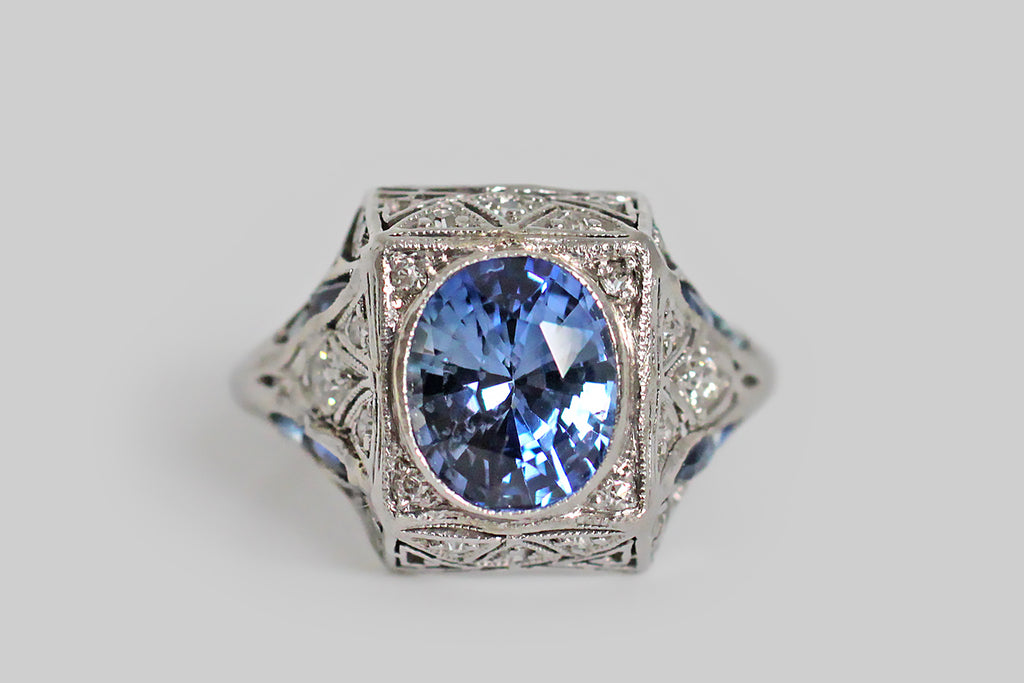 An elegant Art Deco era dinner ring, modeled in platinum, whose primary gemstone is a natural, oval, 2+ carat sapphire. This vibrant, faceted, medium-blue gem is bezel set into the ring's square face, where it is accented by a bevy of small, glittering, old cut diamonds. The ring's highly-dimensional, squarish ring head is decorated (entirely) with delicate, hand-pierced filigree