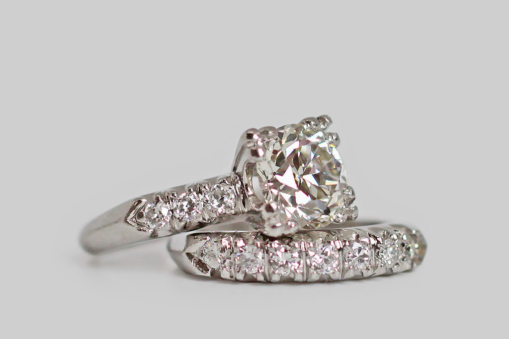 An elegant, 1940s wedding set, modeled in platinum, whose engagement ring features a soulful, 2 carat, old European cut diamond. This lively, hand-cut darling is held in aloft in four, three-lobed prongs and is flanked by trios of smaller diamonds— these supporters are held in fishtail settings across the ring's pitched shoulders. The engagement ring's substantial, knife-edge shank tapers toward the base.