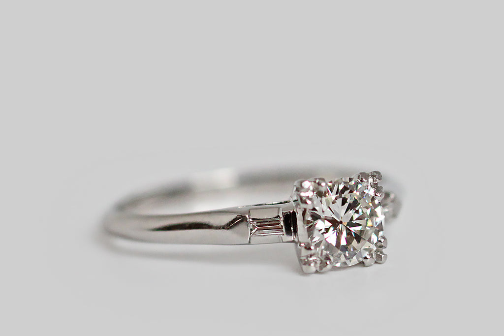 An Art Deco engagement ring, modeled in platinum, whose primary, transitional cut diamond is nested in a low-profile, four-prong basket. This .45 carat diamond is especially bright, lively and clean (F/VVS2). The prongs that hold it aloft are made in a decorative, three-lobed style. A pair of flush set baguette diamonds add interest to the ring's shoulders, and the ring's slender knife-edge shank