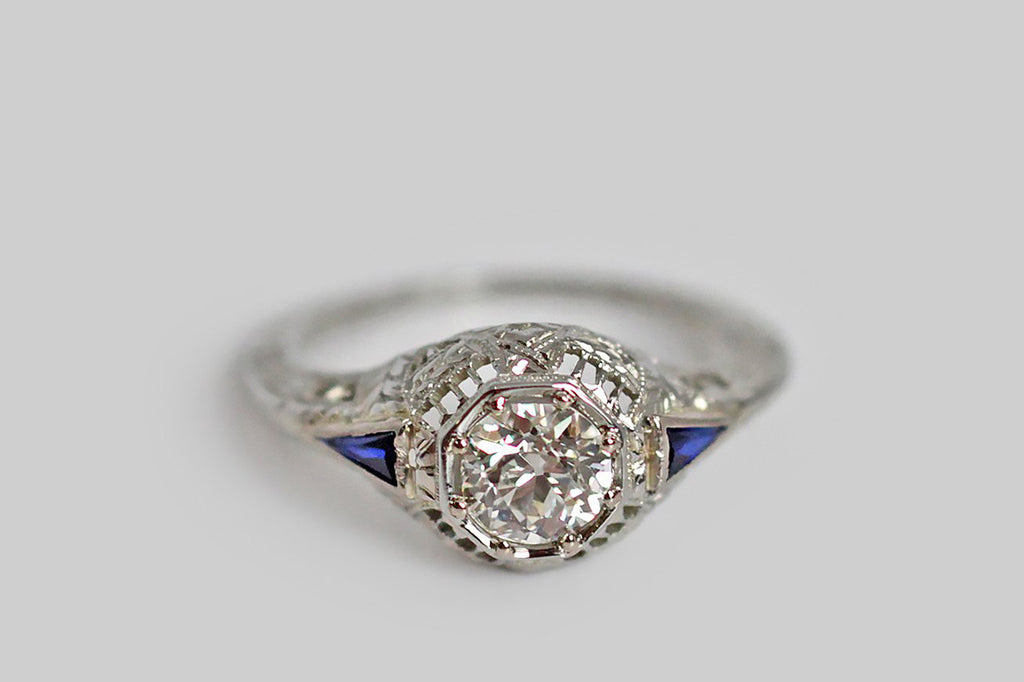 An antique, Art Deco era engagement ring, made in 18k white gold and set with a beautiful .60 carat old European cut diamond. This diamond is bead-set into an octagonal seat, at the center of the softly-bombe ring head. The filigree setting is visually delicate, and boasts a myriad of decorative elements, including knife-wire gallery windows, and criss-crossing