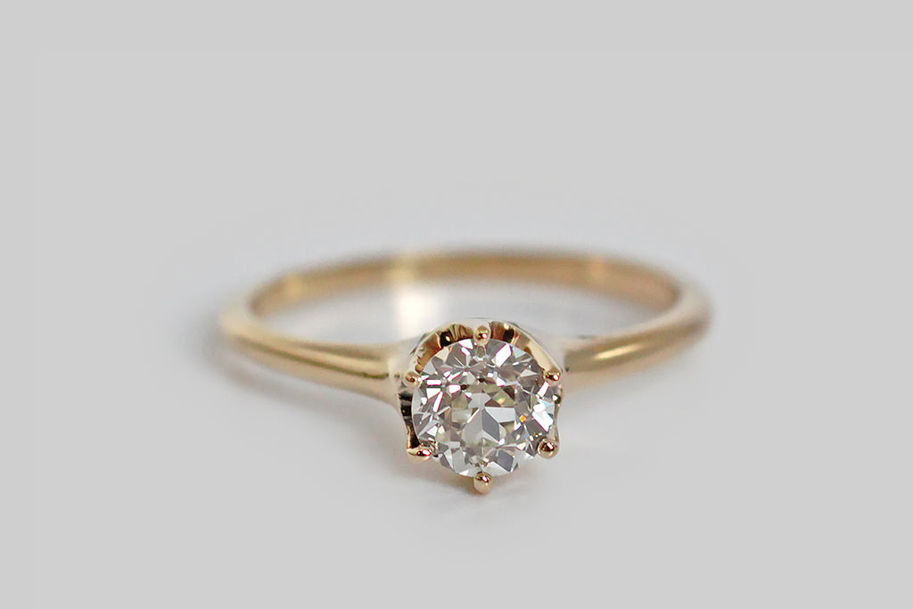 A classic, Edwardian-era engagement ring, modeled in warm 14k yellow gold, and set with a fiery, .75 carat, old European cut diamond. This sleek, six-prong setting holds its diamond very slightly aloft, making this engagement ring lower profile than similar period settings. The half round shank tapers subtly from the shoulder. This OEC diamond is full of fire, and has a nice high color. Clean, elegant, timeless style. Marked with a 14, to indicate fineness.