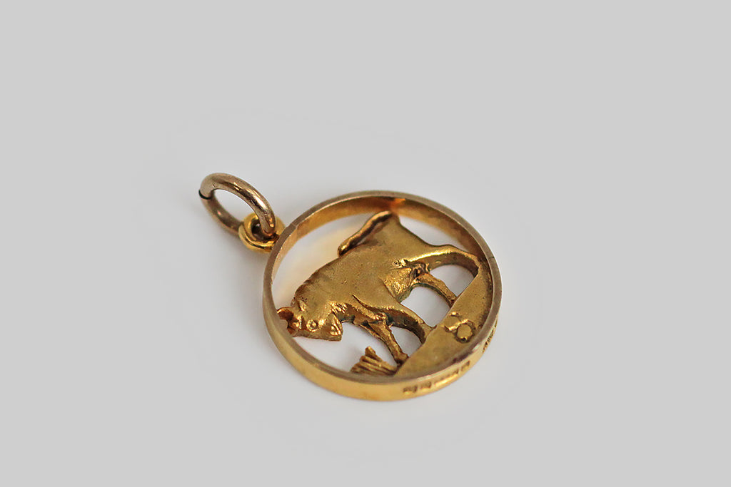 A sweet vintage zodiac charm, made in gilded 9k yellow gold. This miniature Taurus is framed by a flat circle (time is a flat circle, remember!). Inside this circle our bull quietly ponders a clutch of grasses . . . appropriate because this star sign is meant to seek the mutual relationship that exists between matter and spirit. A small astrological Taurus symbol sits on the plane beneath the bull.