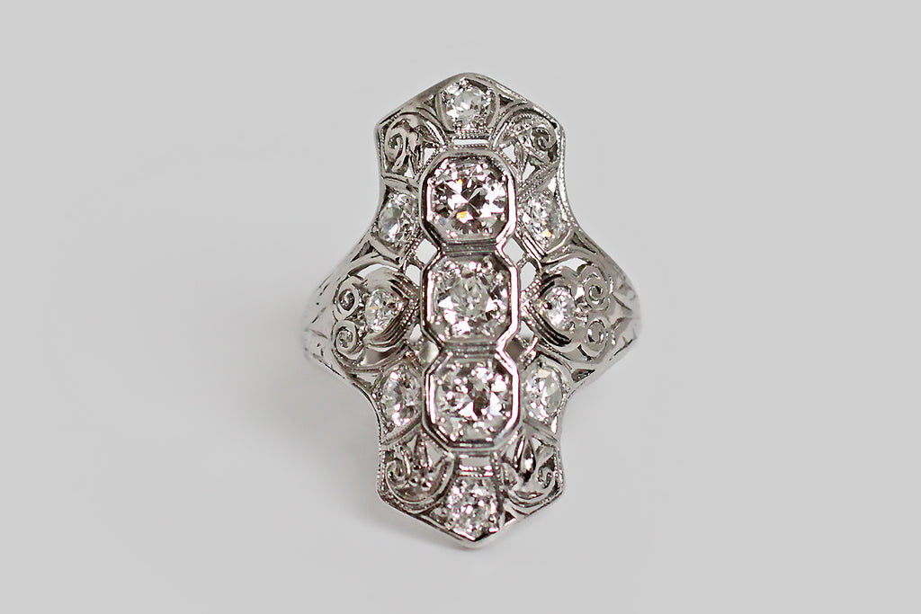 An Art Deco era filigree dinner ring, made in 18k white gold, with a low profile and a dramatic, knuckle-spanning presence. This shapely shield is set with three, primary, old mine cut diamonds, and eight, sizable accent diamonds. The three center stones are bead-set in vertically-stacked, octagonal seats, while the accent diamonds are nested in the curling filigree of the ring face.