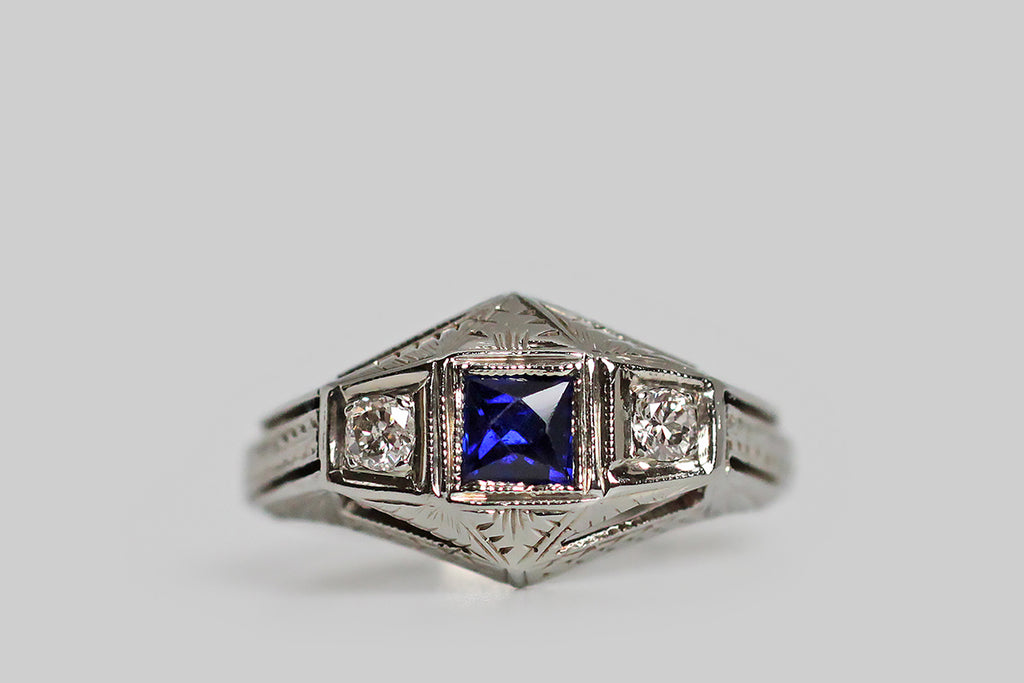A stylized, Art Deco engagement ring, modeled in 18k white gold, whose trio of gems are a French cut, created, blue sapphire, and a sparkling pair of transitional-cut, white diamonds. These gems are oriented in a tidy, horizontal row, where they are held in square seats— each of these seats is finished with a fine milgrain edge. This ring has a unique, dimensional quality, that gives it an aerodynamic feel