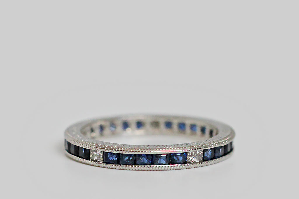 An elegant antique eternity band, modeled in platinum and channel-set with approx 1.5 carats of French cut sapphires. Every five of these deep blue darlings is followed by a sparkling white diamond, in a square, modified step cut (diamond CTW is approx .30). This flat sides of the band are finely engraved with a delicate pattern of swirls, and its edges are finished with milgrain details.