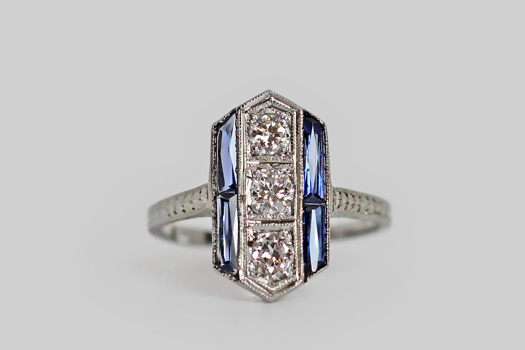 An Art Deco era ring, modeled in 19k white gold, whose elegant, elongated, hexagonal face is set with three sparkling, transitional cut diamonds, and four French cut blue sapphires. The three diamonds are bead set, and organized vertically in the center of the ring face; the sapphires create a feeling of geometry, as they are posted in a linear fashion to either side of the diamond trio. The ring's gallery is decorated with festooning, pierced-and-engraved folate designs.
