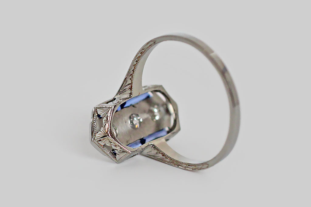 An Art Deco era ring, modeled in 19k white gold, whose elegant, elongated, hexagonal face is set with three sparkling, transitional cut diamonds, and four French cut blue sapphires. The three diamonds are bead set, and organized vertically in the center of the ring face; the sapphires create a feeling of geometry, posted in a linear fashion to either side of the diamond trio. The ring's gallery is decorated with festooning, pierced-and-engraved folate designs.