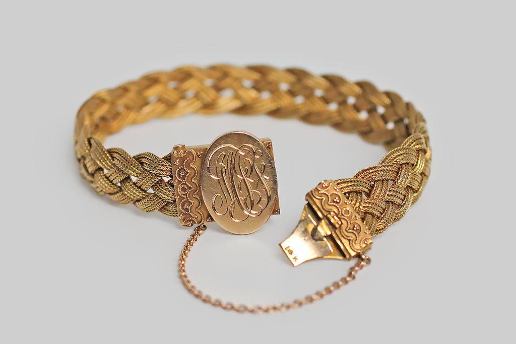 An elegant, Victorian-era, braid-woven bracelet, made in 14k yellow gold, with a monogrammed clasp. The bracelet's centerpiece is hand-engraved with the initials MJG, in curling period script. Rectangular end-pieces, decorated with fine ropework and granulation, done in Etruscan revival style, frame the oval clasp.