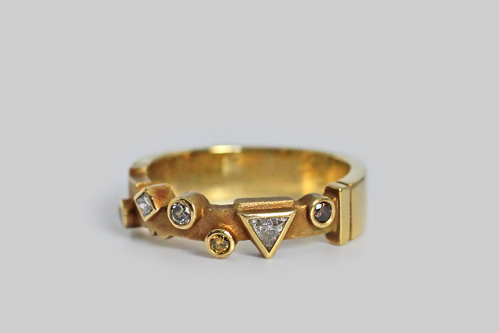 A whimsical 18k gold band, set with an array of fancy colored diamonds, in various shapes. Among these natural, bezel set stones is a cognac round brilliant diamond, two round brilliant canary diamonds, a silver colored round brilliant diamond, and two white diamonds (a triangle and a diamond shape). This playful geometric arrangement sits atop the ring's cutaway face, which has been textured for contrast and features a couple of shapely notches that I especially love.