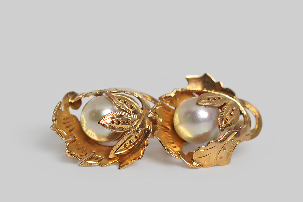 A pair of Retro era drop earrings, modeled in 18k yellow gold, whose highly-dimensional, naturalistic, folate forms were hand-pierced from gold sheet, and moulded (like a shelter) around their lustrous Akoya pearls. These leafy mounts are hand engraved and decorated with beads of granulation. The pearls they shelter read like fruit beneath the leaves