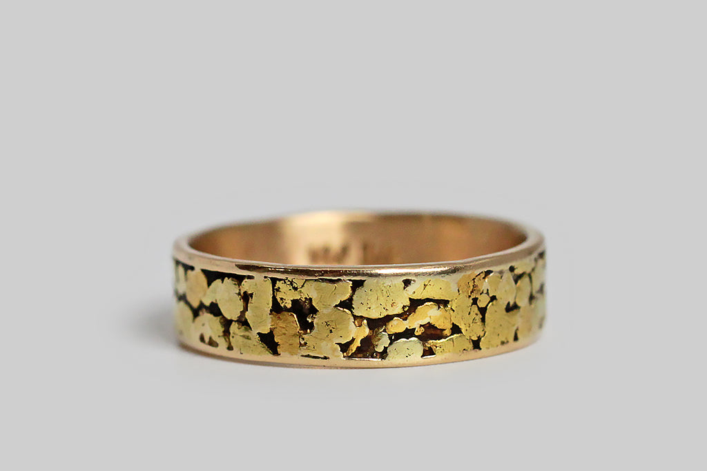 A soulful vintage gold band, modeled in 14k yellow gold and inlaid with natural gold nuggets. This traditional style of gold nugget ring is made by forming a sleeve or trough, with a recessed area to frame the nuggets, which are then soldered in place, as-found, so their original organic shapes and textures remain intact. Because they have not been alloyed with other metals or refined in any way, these gold nuggets test around 22k gold, and have a rich, high color.