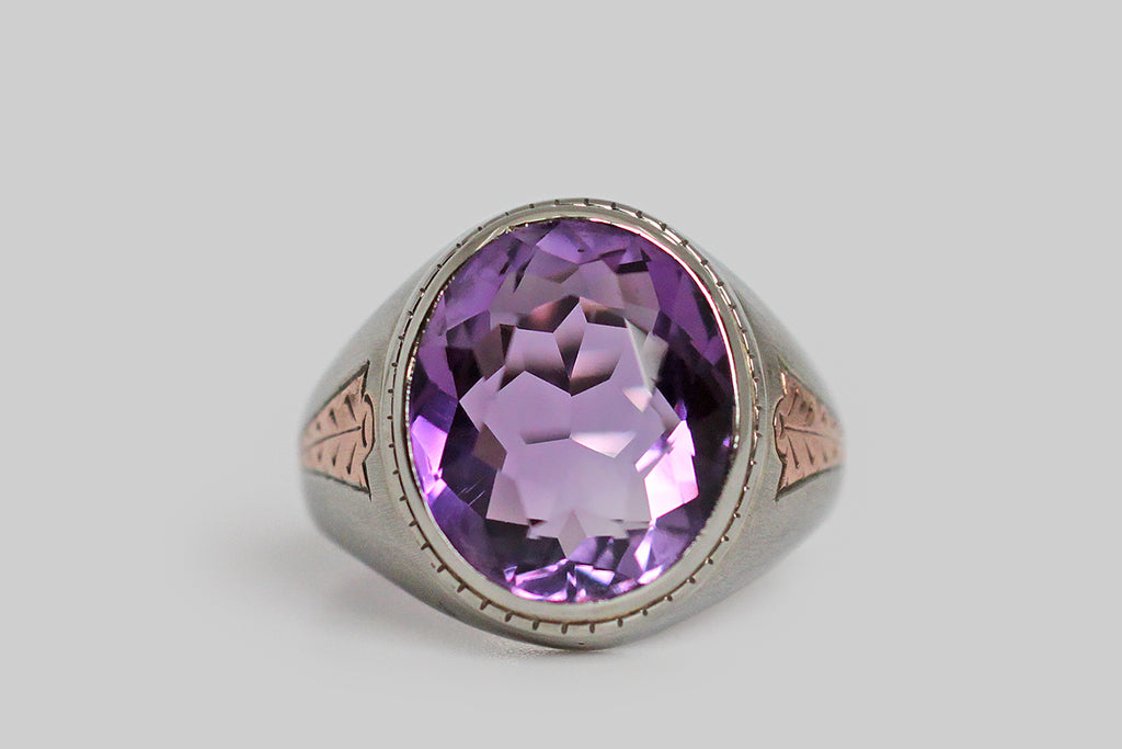 A dandy, streamlined, 1940s ring, modeled in 10k white gold, whose shoulders feature a charming, engraved, rose gold detail. This hand-engraved motif calls to mind an arrowhead, or the tip of a spear— it gives the impression of speed. This ring features a big, beautiful, faceted, amethyst (approx 6.4 carats). The highly-saturated, violet-purple gem is held in a smooth bezel; small hashes decorate the bezel's base.