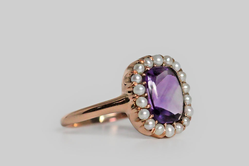 A soulful, Victorian era halo ring, modeled in 14k rose gold, whose principal gem is a cushion-shaped, buff-top amethyst. This vibrant purple amethyst is surrounded by a bevy of iridescent, prong-set, seed pearls. Halo rings from this period are always among our favorite pieces, and this ring's buff-top gemstone, with its faceted pavilion and domed top