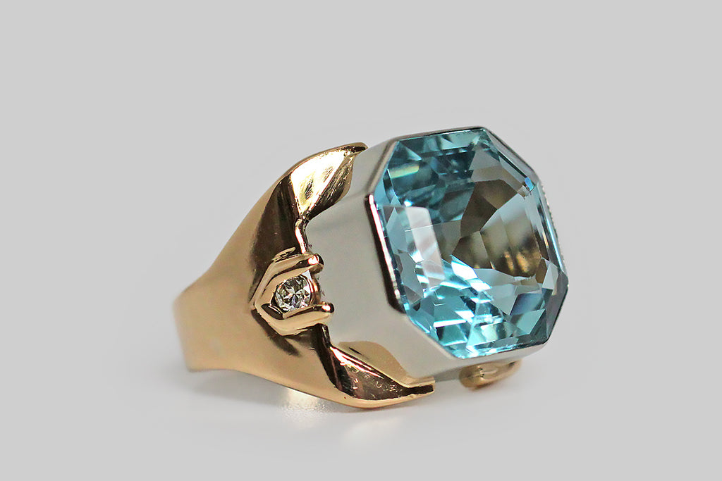 A big, beautiful, Art Moderne ring, modeled in 18k gold, that features a vibrant, 8.25 carat, Asscher cut, aquamarine gem. This mesmerizing gem is a highly saturated, green-inflected, medium blue color— its metallic sheen is intensified by the hall of mirrors effect the Asscher cut imparts. The ring's setting is bold, blocky, and minimal, with a streamlined profile— the oversized bezel is fabricated in white gold, and the shank is fabricated in yellow gold.