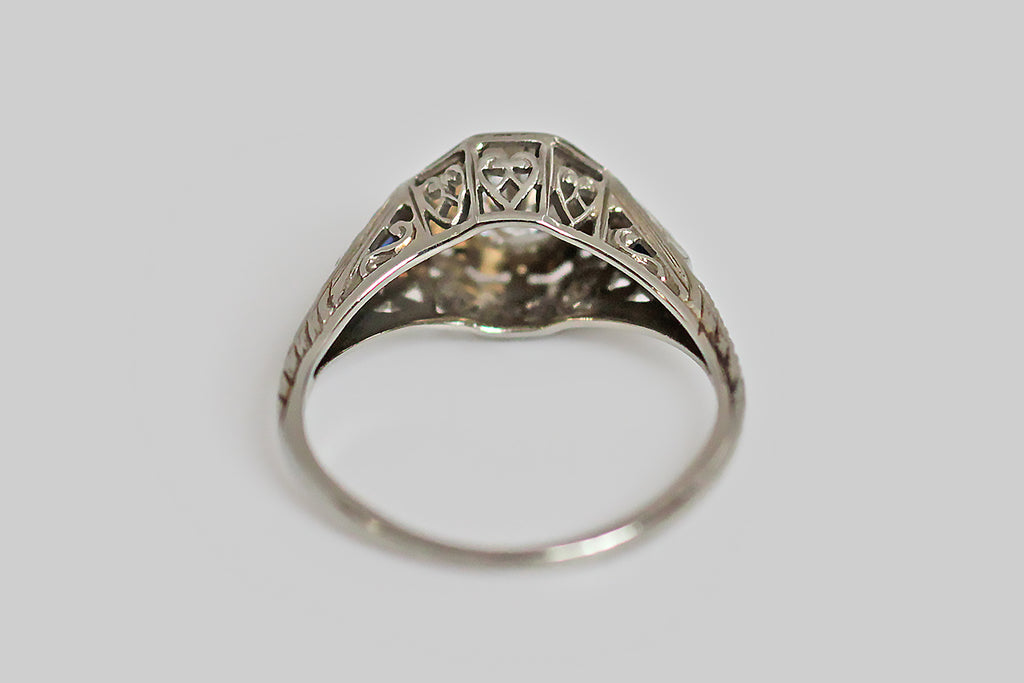 An Art Deco era filigree engagement ring, featuring an extra pretty 1/2 carat Old European cut diamond. This sparkling D/E, VVS OEC is bead-set into a star-shaped seat, in the ring's octagonal head. The ring's shoulders are set with rectangular, french-cut sapphires, and are further embellished with deeply engraved details. Belais