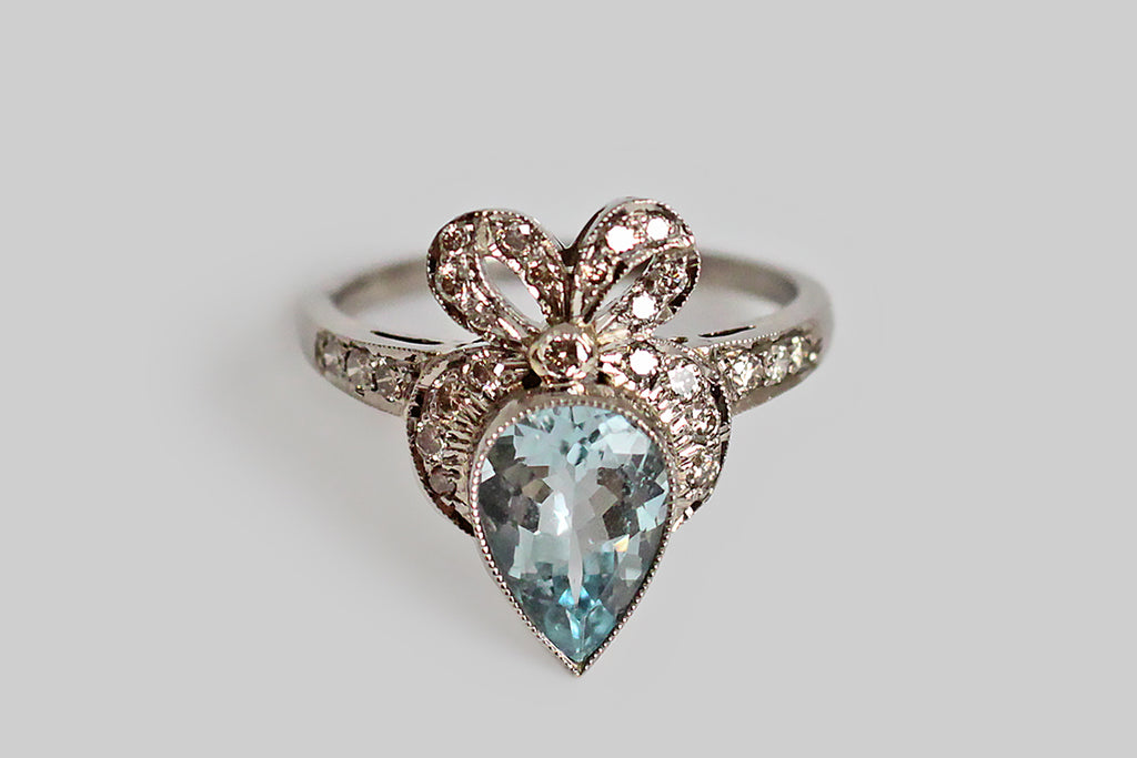"An Art-deco-era ring, made in 18k white gold, and set with a big, icy, aquamarine gem. This pear-shaped aquamarine is crowned with a flouncy, diamond-encrusted bow, in a manner reminiscent of the Victorian-era and its ""crowned heart"" jewelry. These earlier hearts were also created with pear-shaped stones and this traditional motif is meant to symbolize fidelity in a partnership, and to identify the ruler of one's heart!"