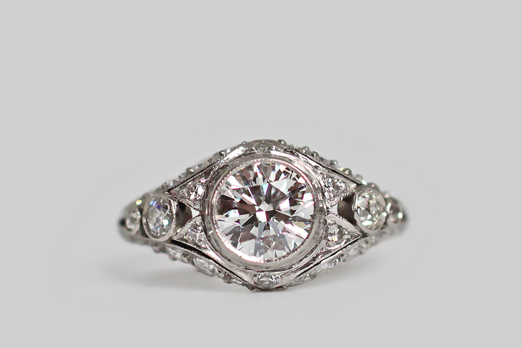A striking Art Deco era engagement ring, modeled in platinum, featuring a 1.09 carat transitional cut diamond. This lovely central gem (F/SI1) rests in a slim milgrain bezel. It is supported by a bevy of smaller diamonds (both early modern brilliant cuts, and old mine cuts), that fill up both sides of the ring's ornate gallery, and decorate its open-work face. We especially love the diamond-set, cutaway, forked-pennant decor that flanks the primary diamond, like a pair of prim little collars.