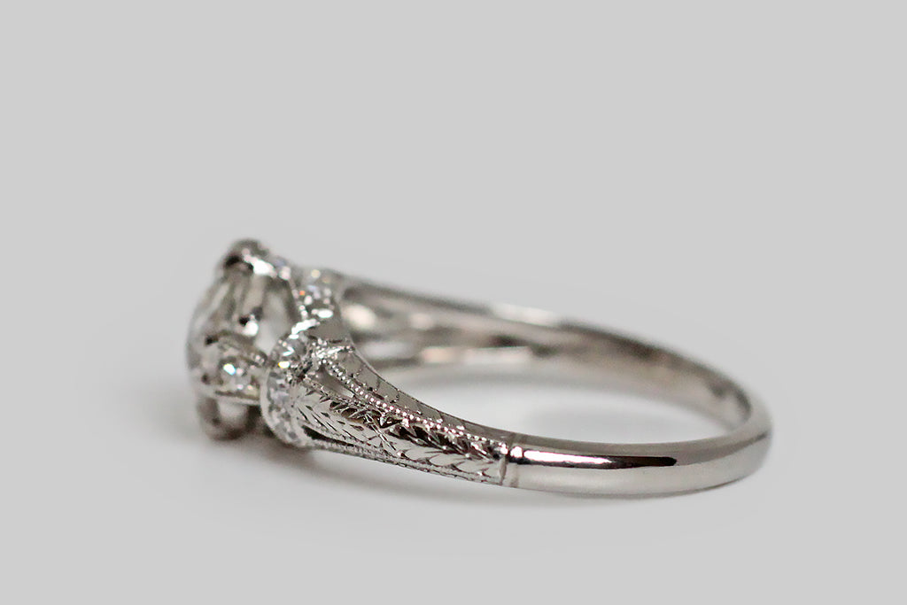 An elegant, Art Deco era engagement ring, modeled in platinum, whose primary gem is a 1.31 carat old mine cut diamond. This lively, central diamond (K-L/SI2) is held in four sets of double prongs. It is supported by a bevy of single cut diamonds, that add sparkle to the ring's intricate shoulders and gallery. This modified cathedral setting features split shoulders that are decoratively bound with diamond-set garters