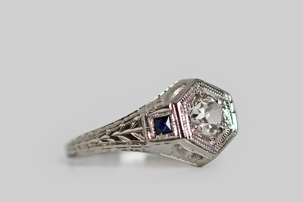 A really lovely 1920s engagement ring, modeled in 18k white gold, whose central gem is a lively, half-carat, old mine cut diamond, which is bead set into the ring's hex-shaped face. This Art Deco era ring is decorated, all-over, with intricate hand-engraving— the shoulders and sides of the ring feature a traditional wheat pattern, while the inter-cardinal points of the ring head are each decorated with an eight-pointed star.