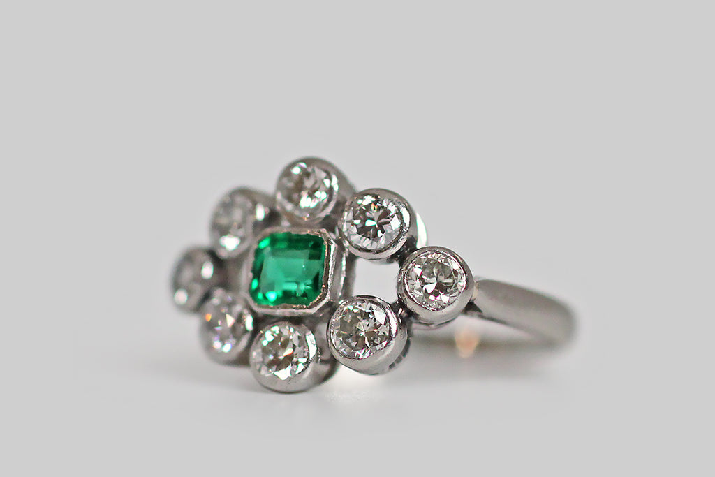 A charming, Art Deco era cluster ring, modeled in platinum--- set with a bevy of early modern brilliant cut diamonds and one vibrant, natural emerald. This old darling's eight white diamonds are set in full bezels and arranged in an east/west navette shape, around the central bezel-set gem, in a manner that suggests an eye. These little bezels are touching, but discreet, and the generous space around them gives this ring a contemporary, geometric vibe.