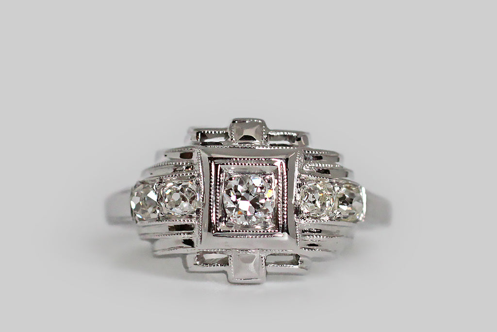 A charming, Art Deco era, five-stone engagement ring, modeled in platinum and set with approx .30 carats of lovely, old cut diamonds. This geometrically-inclined ring calls to mind a small, glittering temple (temple of your love perhaps!). The central transitional cut diamond weighs approx .10 carats