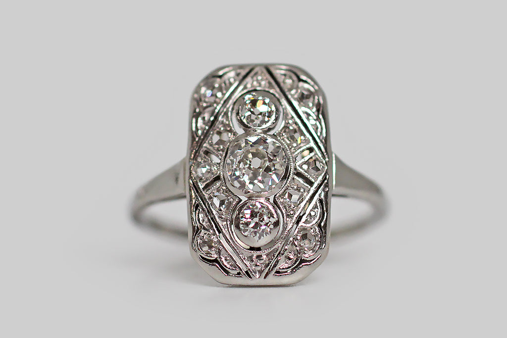 An Art Deco era panel ring, modeled in platinum and set with a bevy of old cut diamonds. The three primary gems are chunky old mine cut diamonds, arranged vertically inside the ring's central diamond-shape, and set in smooth bezels. Rose cut diamond supporters add plenty of glinting sparkle to the rectangular, open-work ring face, where they are bead-set into clusters of circular shapes, and smaller diamond shapes. This low profile darling would make a charming alternative engagement ring.