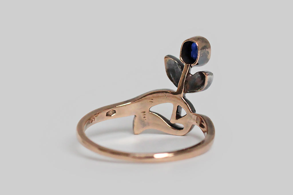 A sweet, Art Nouveau era ring, whose old cut blue sapphire is a flower bud, nodding above a pair of silver-topped, rose cut diamond set leaves. This ring is made in 14k rose gold, with a swooping, asymmetrical band, that curves gracefully and then jags, here and there. Its glinting rose cut diamonds are smoky, and rustic. These small, poetic, Art Nouveau pieces are few and far between.