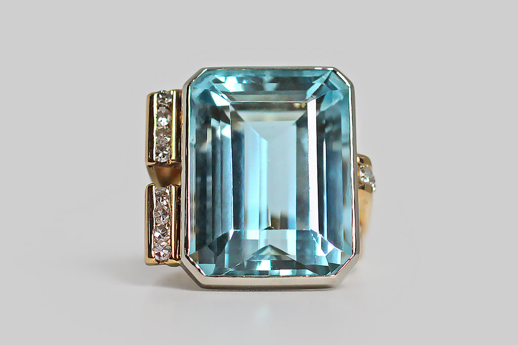 A bold vintage, modernist ring, modeled in 18k gold, featuring a magnificent, twenty-one carat, step-cut aquamarine gem. This vibrant gem is held in a smooth, low-profile, white gold bezel, that perches atop the ring's fully-round shank on four slender stilts. The ring's split shank is modeled in yellow gold, and is fully round. It's shoulders are innovative and asymmetrical— one side features a broad pair of elegant, tapering laths, whose front-facing ends are channel-set with white, brilliant cut diamonds