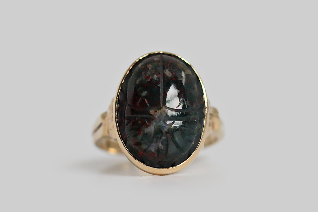 A charming antique ring, made in 10k yellow gold, and set with a bloodstone gem, carved in the likeness of a scarab beetle. This ring dates to the 1920s. Made by Ostby & Barton, when interest in ancient Egypt was enlivened by the excavations of tombs in The Valley of the Kings, its shoulders are decorated with a dimensional scroll design, and the half round shank tapers toward the base.