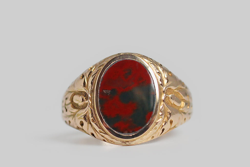 A striking, 1940s, bloodstone signet ring, modeled in 10k yellow gold, whose shoulders feature a deeply-carved decor of oak leaves and acorns. This carving is of very fine quality, with expressive lines, subtle variations, and a stippled ground that creates visual depth in the relief. Acorns symbolize growth and potential, while oak leaves stand for strength, endurance and fertility. Remember the old adage: all the wonder in a mighty oak grows from a single acorn.