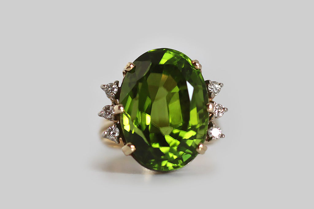 "A glamourous, vintage, 1960s cocktail ring, featuring a big, exceptional, once in a lifetime, Burmese peridot. This gem is highly-saturated, grass green, and crystal clear— its weight is approximately 19 carats. The peridot is held aloft in an 18k yellow gold setting, whose open, cage-like shape is iconic of the period. Three, round, brilliant-cut, white diamonds adorn either side of the rare central gemstone. The GIA refers to peridot as ""the extreme gem,"" because it is one of only two gemstones (diamond"