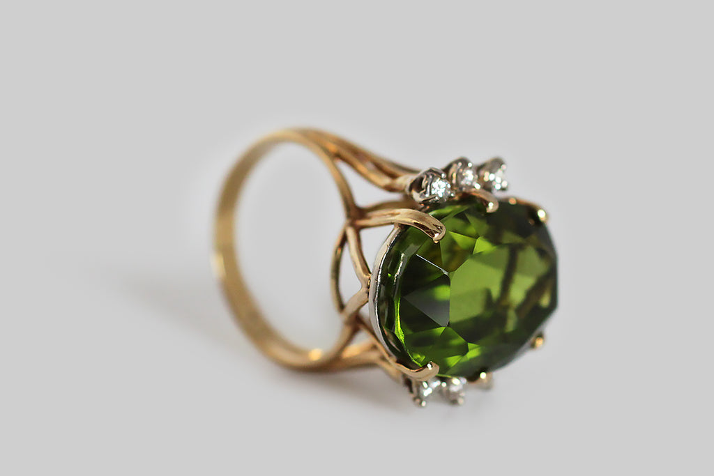 "A glamourous, vintage, 1960s cocktail ring, featuring a big, exceptional, once in a lifetime, Burmese peridot. This gem is highly-saturated, grass green, and crystal clear— its weight is approximately 19 carats. The peridot is held aloft in an 18k yellow gold setting, whose open, cage-like shape is iconic of the period. Three, round, brilliant-cut, white diamonds adorn either side of the rare central gemstone. The GIA refers to peridot as ""the extreme gem,"" because it is one of only two gemstones (diamond i"
