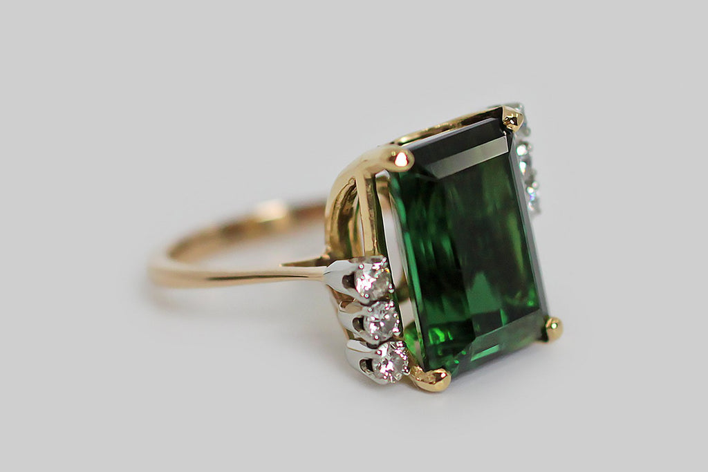 An elegant, mid 20th century cocktail ring, modeled in 18k yellow gold and platinum, and featuring a magnificent, highly saturated chrome tourmaline. This 12 carat, step-cut gem is held in four corner corner mount prongs, and is flanked by two trios of brilliant-cut white diamonds.