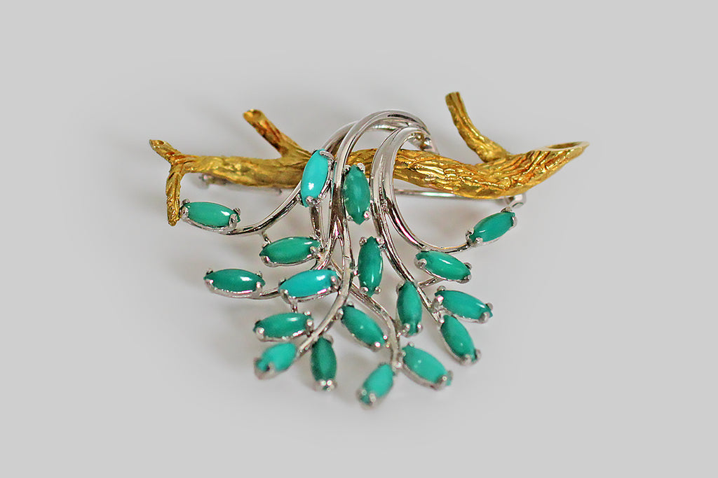 A serene and whimsical mid-twentieth-century brooch, made in 18k gold to recall a branch, draped with cascading foliage. The branch in this composition is modeled in vibrant yellow gold and is realistically textured; the foliate elements are small marquise-shaped chrysocolla cabochons— each of these gems (there are eighteen, in total) is set in a delicate, white gold four-prong basket setting.